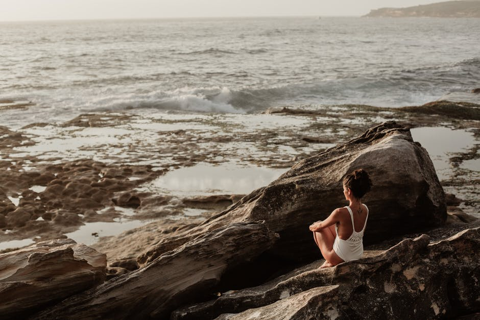 A person sitting on a rock near the ocean